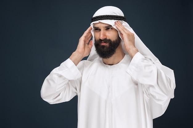 Halblanges porträt des arabischen saudischen geschäftsmannes auf dunkelblauem studio