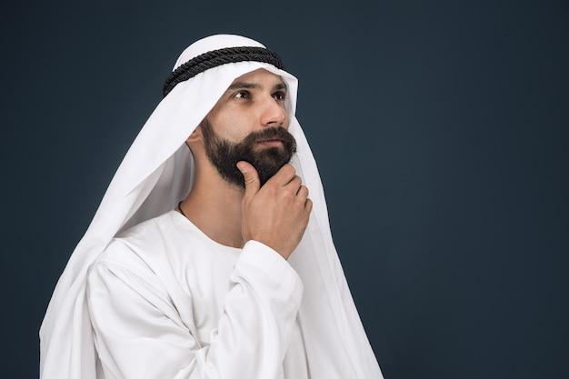 Halblanges porträt des arabischen saudischen geschäftsmannes auf dunkelblauem studiohintergrund. junges männliches modell stehend und sieht nachdenklich aus. konzept von geschäft, finanzen, gesichtsausdruck, menschlichen emotionen.