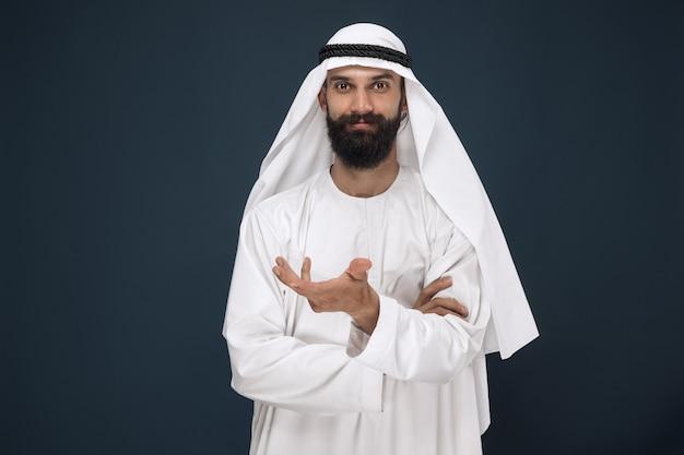 Halblanges porträt des arabischen saudischen geschäftsmannes auf dunkelblauer studiowand