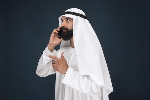 Halblanges porträt des arabischen saudischen mannes auf dunkelblauer studiowand. männliches modell, das smartphone verwendet und einen anruf tätigt. konzept von geschäft, finanzen, gesichtsausdruck, menschlichen emotionen, technologien.