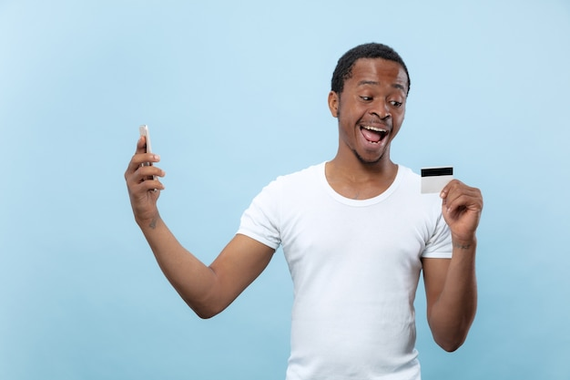 Halblanges porträt des jungen afroamerikanermannes im weißen hemd, das eine karte und ein smartphone auf blauem hintergrund hält. menschliche emotionen, gesichtsausdruck, anzeige, verkauf, finanzen, online-zahlungskonzept.