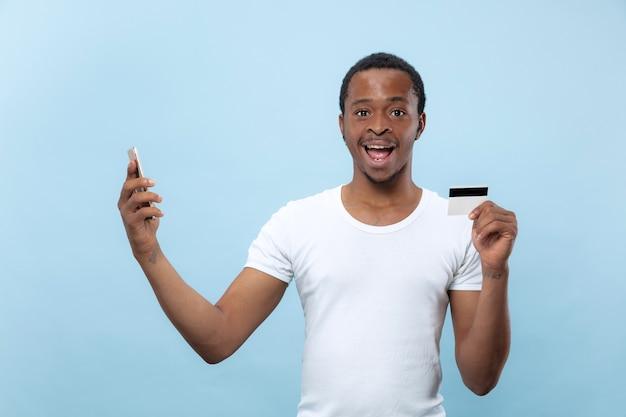 Halblanges porträt des jungen afroamerikanermannes im weißen hemd, das eine karte und ein smartphone auf blauem raum hält