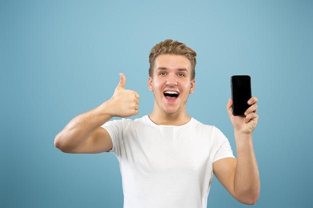 Halblanges porträt des kaukasischen jungen mannes auf blauem studiohintergrund. schönes männliches modell im hemd. konzept der menschlichen emotionen, gesichtsausdruck, verkauf, anzeige. telefonbildschirm, zahlung, wetten anzeigen.