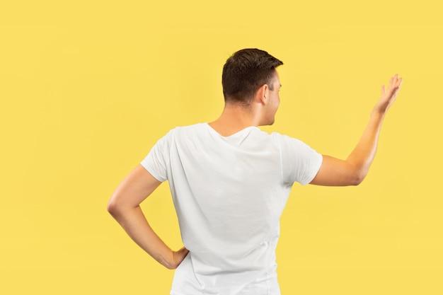 Halblanges porträt des kaukasischen jungen mannes auf gelbem studiohintergrund. schönes männliches modell im hemd. konzept der menschlichen emotionen, gesichtsausdruck, verkauf, anzeige. etwas zeigen und zeigen.