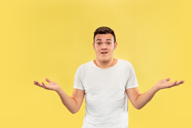 Halblanges porträt des kaukasischen jungen mannes auf gelbem studiohintergrund. schönes männliches modell im hemd. konzept der menschlichen emotionen, gesichtsausdruck, verkauf, anzeige. etwas zu zeigen, sieht unsicher aus.