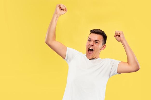 Halblanges porträt des kaukasischen jungen mannes auf gelbem studiohintergrund. schönes männliches modell im hemd. konzept der menschlichen emotionen, gesichtsausdruck, verkauf, anzeige. feiern, anrufen, schreien.