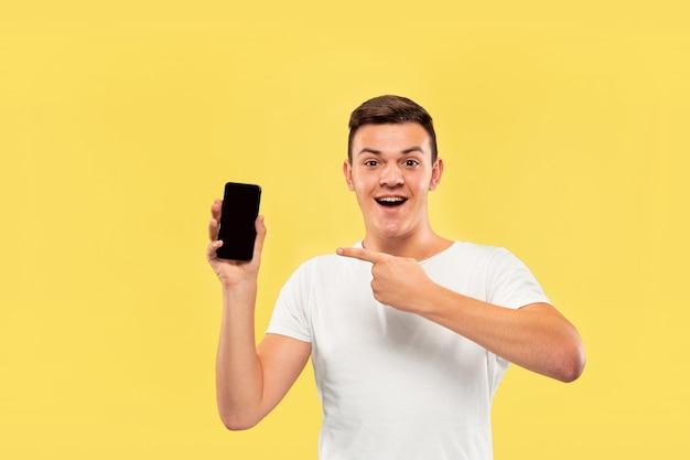 Halblanges porträt des kaukasischen jungen mannes auf gelbem studiohintergrund. schönes männliches modell im hemd. konzept der menschlichen emotionen, gesichtsausdruck, verkauf, anzeige. telefonbildschirm anzeigen und lächeln.