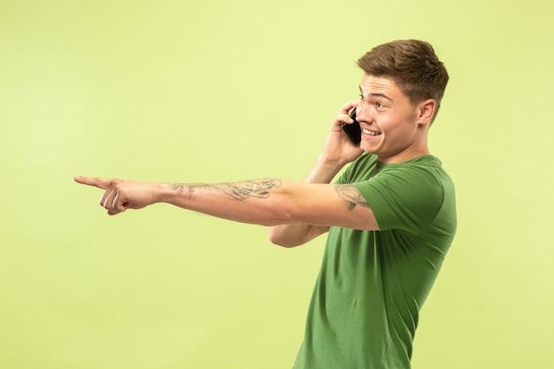 Halblanges porträt des kaukasischen jungen mannes auf grünem studiohintergrund. schönes männliches modell im hemd. konzept der menschlichen emotionen, gesichtsausdruck, verkauf, anzeige. am telefon sprechen und zeigen, lächeln.