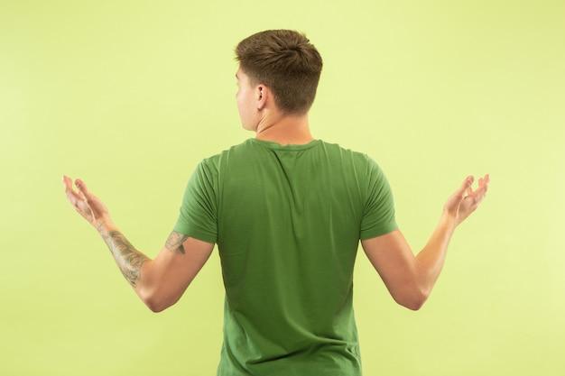 Halblanges porträt des kaukasischen jungen mannes auf grünem studiohintergrund. schönes männliches modell im hemd. konzept der menschlichen emotionen, gesichtsausdruck, verkauf, anzeige. etwas zeigen und zeigen.