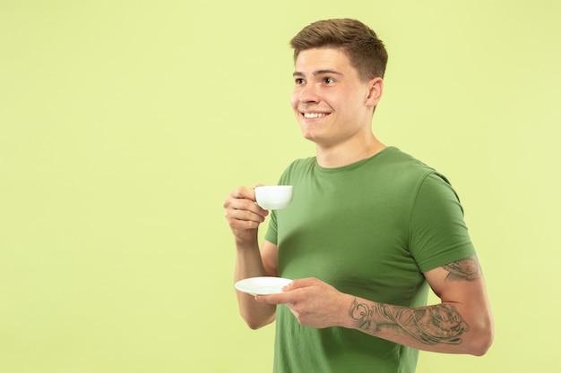 Halblanges porträt des kaukasischen jungen mannes auf grünem studiohintergrund. schönes männliches modell im hemd. konzept der menschlichen emotionen, gesichtsausdruck, verkauf, anzeige. kaffee oder tee trinken.