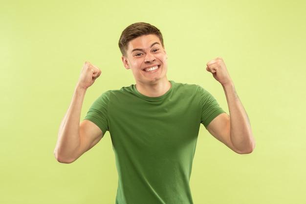 Halblanges porträt des kaukasischen jungen mannes auf grünem studiohintergrund. schönes männliches modell im hemd. konzept der menschlichen emotionen, gesichtsausdruck, verkauf, anzeige. verrückt glücklich, feierend, geschockt.