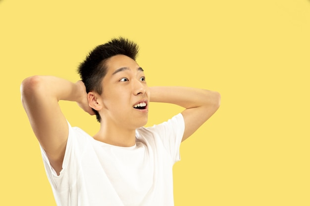 Halblanges porträt des koreanischen jungen mannes auf gelb