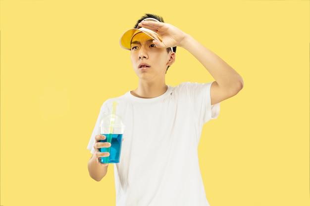 Halblanges porträt des koreanischen jungen mannes auf gelbem studiohintergrund. männliches modell im weißen hemd und in der gelben kappe. cocktail trinken. konzept der menschlichen gefühle, ausdruck, sommerzeit, urlaub, wochenende.