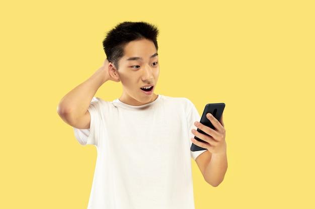 Halblanges porträt des koreanischen jungen mannes auf gelber wand