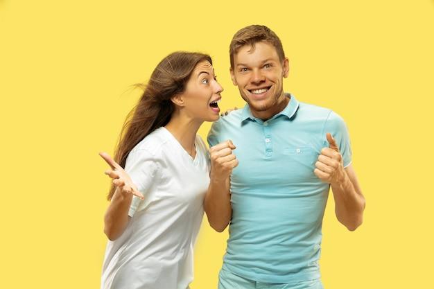Halblanges porträt des schönen jungen paares. frau und mann in hemden feiern und zeigen das zeichen von ok. gesichtsausdruck, menschliches gefühlskonzept. trendige farben.