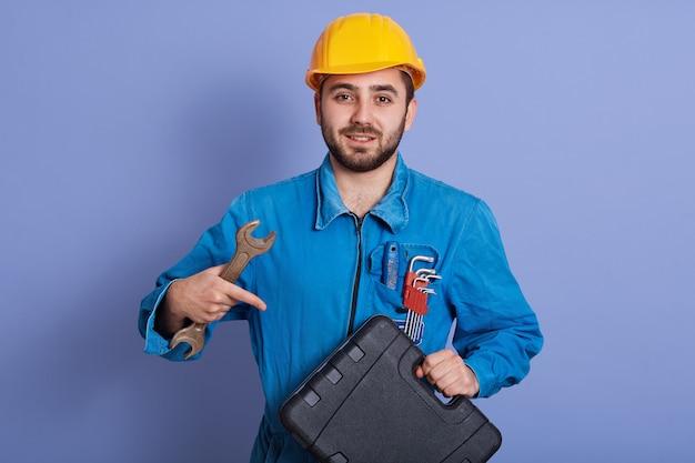 Halblanges porträt eines bärtigen mannes, der den schraubenschlüssel in der hand hält und mit dem zeigefinger auf den werkzeugkasten in der anderen hand zeigt, isoliert über blau posiert, sieht ruhig aus, kleidet uniform und helm.