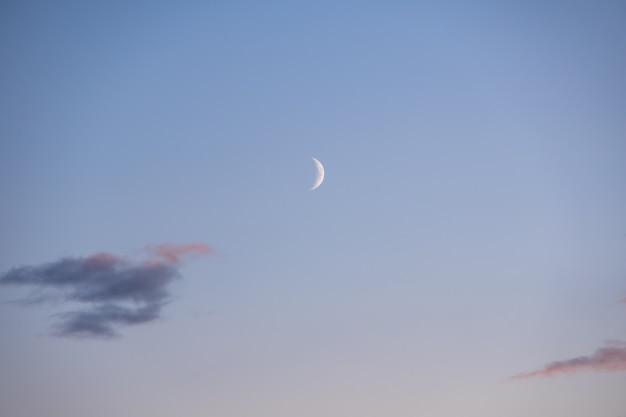 Halbmond am morgen auf rosa himmel mit wolken, blaue stunde. träumen sie von einem magischen abendhimmel mit mond und wolken. natürlicher himmelshintergrund für ihre fotos