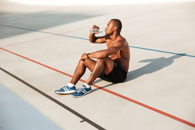 Halbnackter muskulöser afrikanischer sportler, der sich ausruht