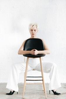 Halbnacktes modell in weißer hose sitzt auf einem schwarzen stuhl