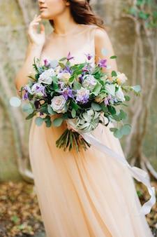 Halbporträt einer braut in einem beigen kleid und einem schönen rosenstrauß in ihren händen
