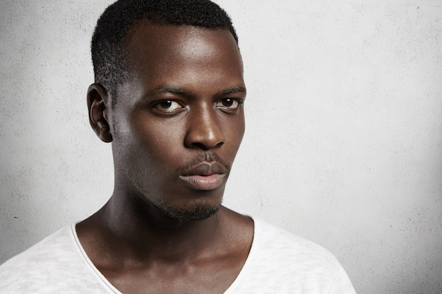 Halbprofilaufnahme eines gut aussehenden afroamerikaners mit kleinem bart, der lässiges t-shirt trägt, das mit ernstem ausdruck gegen weiße wand posiert, unzufrieden mit unangenehmen nachrichten