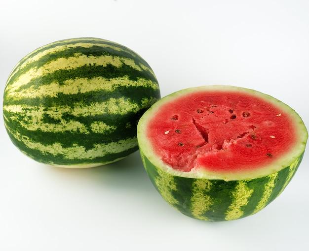 Halbreife wassermelone mit rotem saftigem fruchtfleisch und samen und einem ganzen grün