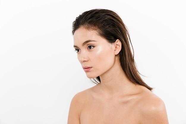 Halbumdrehungsporträt der nackten asiatischen frau mit dem nassen braunen haar, das beiseite schaut, lokalisiert über weiß