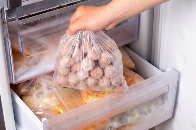 Halbzeuge, gefrorene fleischbällchen, fleischpastetchen in plastiktüte im kühlschrank, horizontal