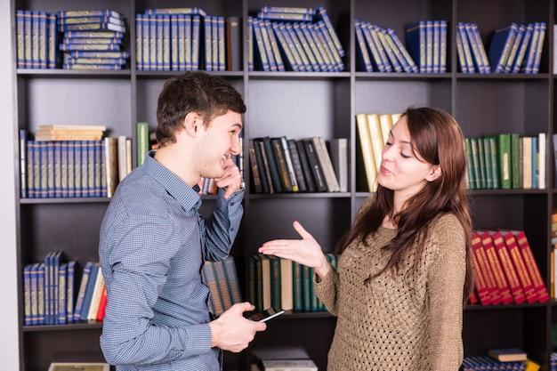 Half body shot von glücklichen jungen liebhabern, die in der bibliothek vor den bücherregalen diskutieren.