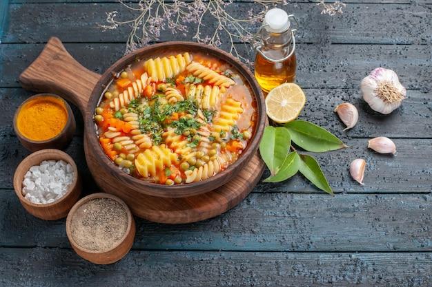 Half-draufsicht spiral-nudelsuppe leckeres essen mit verschiedenen gewürzen auf dunkelblauem schreibtisch suppenfarbe italienische nudelgerichtsküche