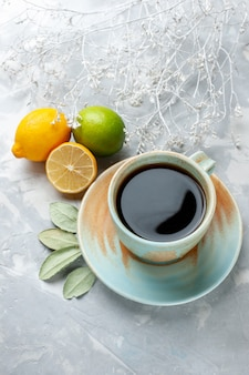 Half-top-view-tasse tee mit frischen zitronen auf dem weißen schreibtisch obst frische zitrusfrüchte exotisch