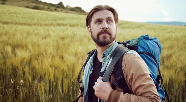 Half-turn-porträt eines bärtigen rucksacktouristen, der in einer landschaft wandert, die landschaft bewundert