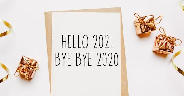 Hallo 2021 bye bye 2020 notiz mit geschenken und goldband auf frohen weihnachten und neujahrskonzept