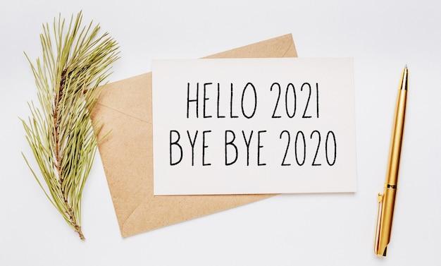 Hallo 2021 bye bye 2020 notiz mit umschlag, fichtenzweig und goldstift auf weiß
