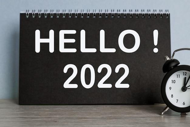 Hallo 2022, wecker, schwarzes notizbuch mit text, auf blauem hintergrund, zeit läuft weg.