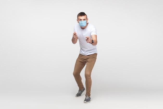 Hallo du. ganzaufnahme eines ernsten jungen mannes in weißem hemd mit chirurgischer medizinischer maske, der mit ernstem gesicht auf die kamera schaut und zeigt. indoor-studioaufnahme, isoliert auf grauem hintergrund
