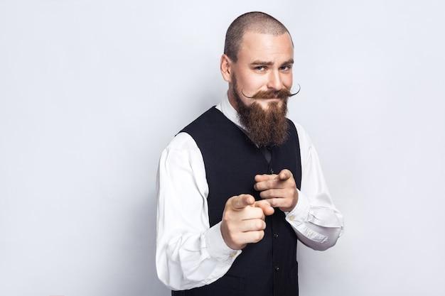 Hallo du. gut aussehender geschäftsmann mit bart und schnurrbart am lenker, der in die kamera schaut. studioaufnahme, auf grauem hintergrund.