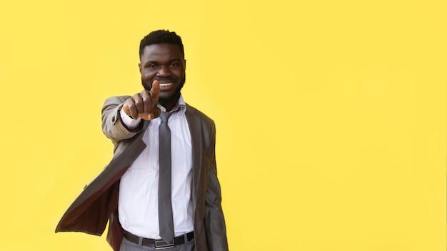 Hallo du. positiver afrikanischer kerl, der finger auf kamera zeigt, die auf gelbem hintergrund aufwirft. studioaufnahme