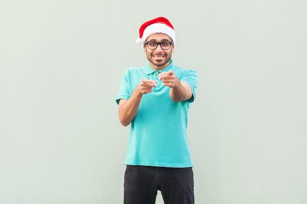 Hallo du! sein weihnachtsmann! bärtiger mann in weihnachtsmütze und brille, der mit dem finger zeigt und mit einem zahnigen lächeln in die kamera schaut. auf grauem hintergrund. innenaufnahme, studioaufnahme