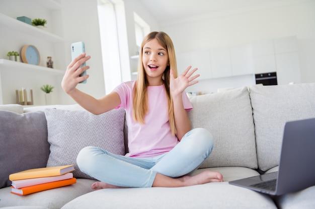 Hallo follower. foto in voller länge von kind mädchen studie fernbedienung ruhe entspannen smartphone verwenden haben online-instagram-sendewellen-hand sagen, hallo sit-beine gekreuzten komfort-couch im haus drinnen
