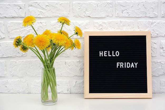 Hallo freitag-wörter auf tafel und blumenstrauß des gelben löwenzahns blüht