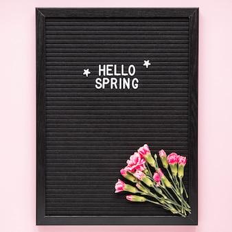 Hallo frühlingsaufschrift mit rosa blumen auf schwarzem brett