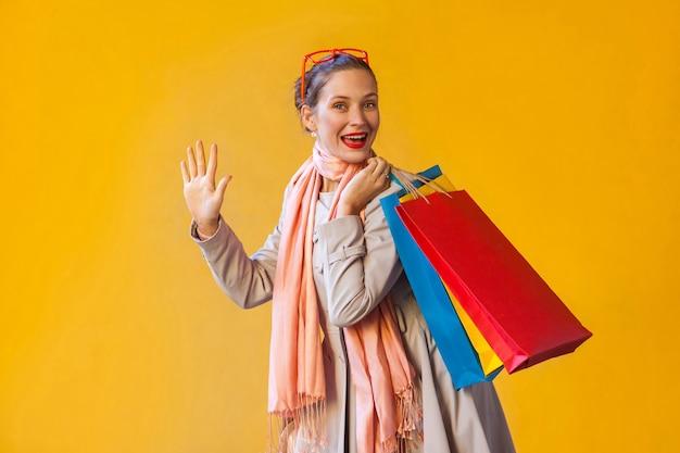 Hallo! glückliche junge erwachsene frau mit sommersprossen, haare sammeln, kamera betrachten, hand hoch, viele einkaufstaschen halten, guten einkaufstag genießen. studioaufnahme, gelber hintergrund