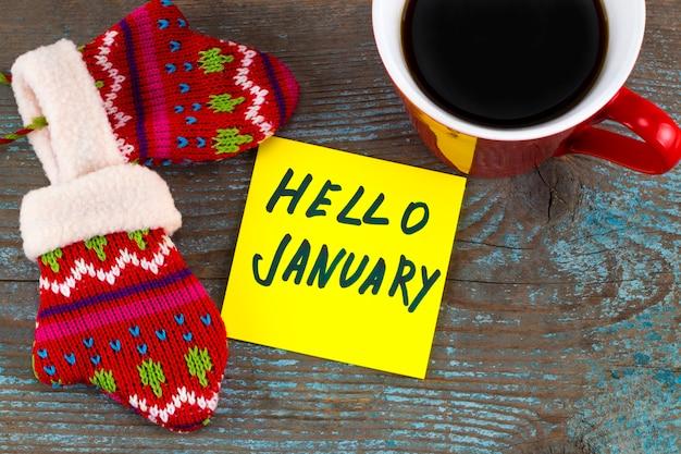 Hallo januar - handschrift in schwarzer tinte auf einer haftnotiz mit einer tasse kaffee und handschuhen, neujahrsvorsätze.