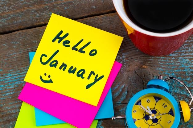 Hallo januar - handschrift in schwarzer tinte auf einer haftnotiz mit einer tasse kaffee und wecker, neujahrsvorsätze-konzept.