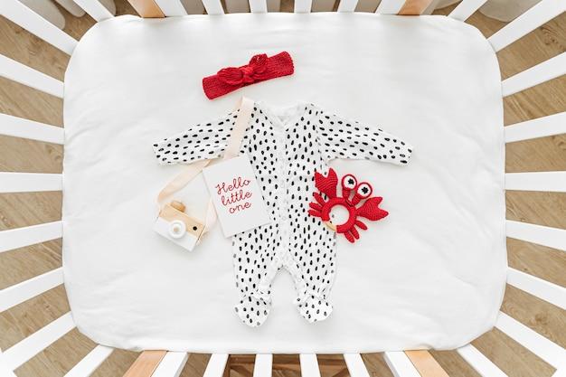 Hallo kleiner. netter babybody mit spielzeug. set kinderkleidung und accessoires. mode neugeborenes. flache lage, ansicht von oben