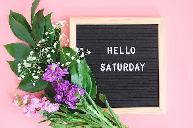 Hallo samstag text auf schwarzem briefbrett und strauß bunte blumen auf rosa hintergrund. konzept happy saturday.