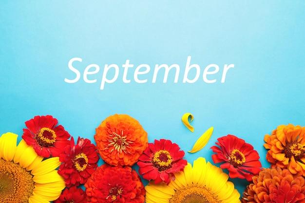 Hallo september-nachricht mit verschiedenen herbstblumen auf blauem hintergrund. herbstkomposition