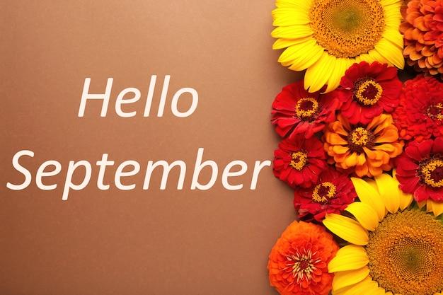 Hallo september-nachricht mit verschiedenen herbstblumen auf braunem hintergrund.