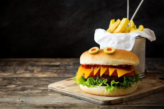 Halloween-burgermonster mit pommes-frites auf hölzernem tabellen-kopienraum